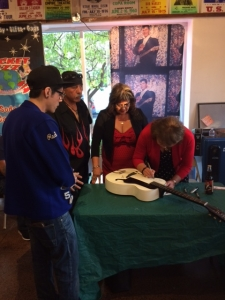 <p>Rocket Fizz held an event honoring the late rock legend Ritchie Valens. In this photo, Ritchie's sisters Irma and Connie are autographing a guitar for a fan. Hundreds of people showed up to meet Ritchie's family and to celebrate what would have been Ritchie's 76th birthday.</p>