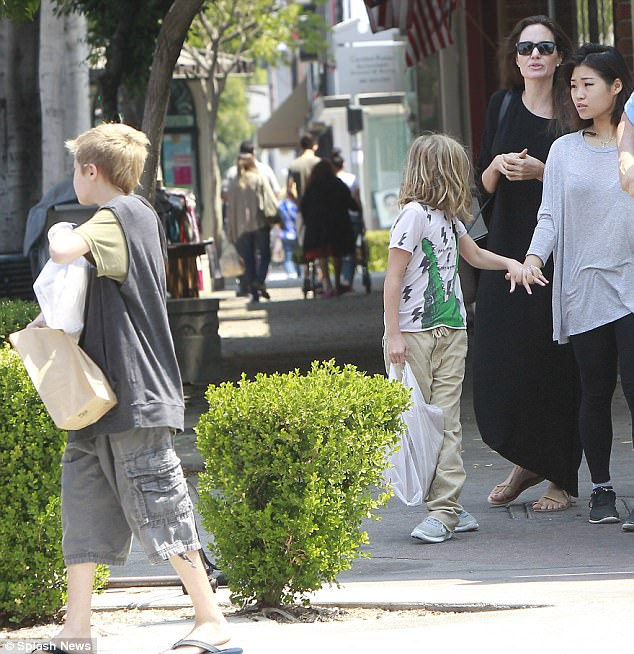 Angelina Jolie rocks chic maxidress as she treats daughters Shiloh, 11, and Vivienne, nine, to candy store trip... amid reports she 'won't reconcile with Brad Pitt due to child abuse claims'