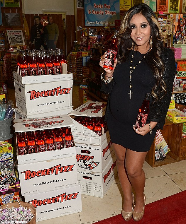 A very different type of bubbly! Snooki shows off her baby bump in a black minidress as she launches her own cherry soda fizz